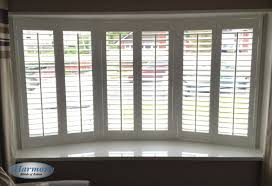 faux wood shutters in a bay window harmony blinds of bolton and