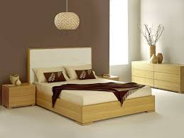 smooth brown wooden single bed with cream bed sheet and white
