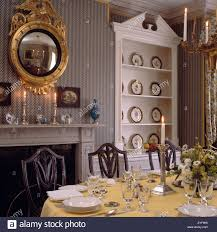 Mirror Over Dining Room Table - diningroom with grey striped wallpaper and gilt mirror over