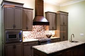 lovely kitchen made of brown wooden cabinets and marble