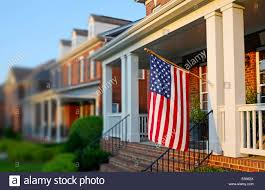 American House Flag An American Flag Hangs From A Front Porch In A Neighborhood Of