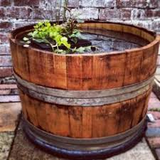 half whiskey barrel planter turned up side down burlap and glass