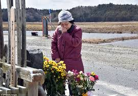 Heartache  A relative of tsunami victims offers a flower bouquet at the altar in Namie
