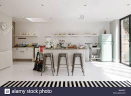 open plan white tiled kitchen with barstools and retro fridge