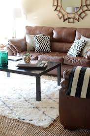 rug on top of carpet layered area rug over carpet in living room with brown sofa and