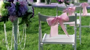 white bow blocking the aisle of an empty outdoor wedding