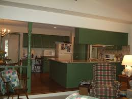 dark green wooden kitchen cabinet connected by brown wooden floor