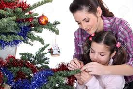 mom and daughter decorating the christmas tree stock photo