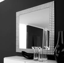 square mirror with silver steel frame on the black wall of awesome