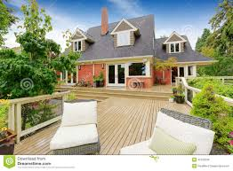 brick house with walkout deck patio area with wicker chairs stock