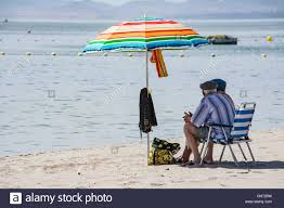 Beach Shade Umbrella Elderly Couple Sit Under The Shade Of A Umbrella On The Beach At