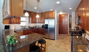 custom home interiors kitchen with solid granite countertops under cabinet lighting and decorative pendant lighting