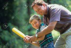 cropped image of a father showing his young son how to hold and