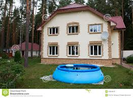 Backyard Inflatable Pool by Big House Out Of Town And An Inflatable Pool Royalty Free Stock