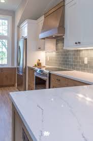 kitchen white quartz countertops and the backsplash is carrera