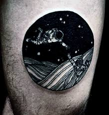 little space themed black and white round tattoo on thigh