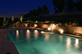 outdoor lighting on in ground pool waterfall and stone wall