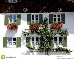 house with six windows and red flowers in oberammergau in bavaria