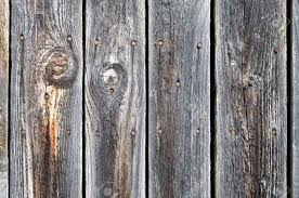 black painted weathered wooden fence with rusty nail heads stock