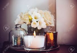 bouquet of white flowers in a vase candles on vintage copper