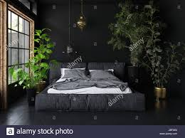 room with black walls wide bed in dark room with black walls and floor tall potted