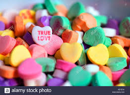 heart shaped candy small heart shaped candies in a pile with true written on one