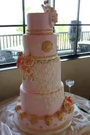 a gold ornament and white lace wedding cake and a tinga tinga