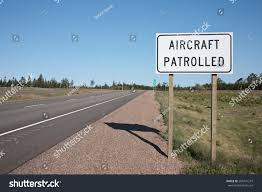 aircraft patrolled sign beside highway stock photo 285431219