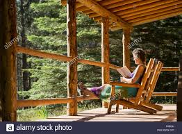 woman reading a book on the porch of a log cabin at the minam