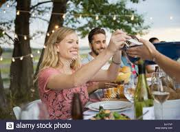 friends sitting together at an outdoor dinner party stock photo