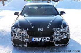 4 series spied with less camo taking a break next to an audi a5