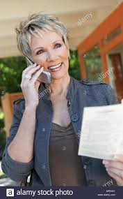 elegant mature woman elegant mature woman using mobile phone holding brochure stock photo