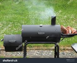 charcoal offset smoker during backyard cookout stock photo