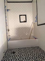 white wall paint bathtub faucet head ceramic flooring tile mirror