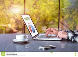 person working at wooden desk on computer coffee phone stock photo