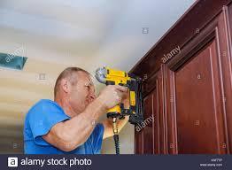 carpenter brad using nail gun to crown moulding on kitchen