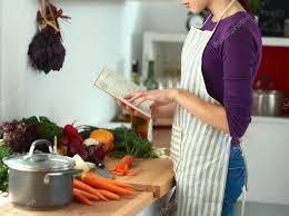 recherche recette de cuisine femme lisant le livre de recettes dans la cuisine à la