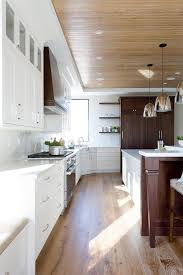 brown and white kitchen cabinets brown stained wood panel refrigerator doors transitional kitchen
