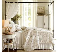 black metal iron canopy bed frame with pretty bed and round side
