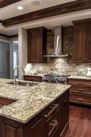 best 25 stone backsplash ideas on pinterest stacked stone custom wood cabinets and gray stone countertops are top of the line finishes featured in this elegant yet rustic kitchen a stacked stone backsplash
