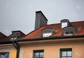 close up of houses with red tile roof chimney attic windows