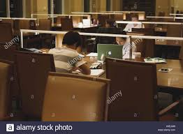 study table for college students college students seated at study tables work from notebooks and