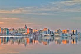 the madison wisconsin skyline at dusk reflected in lake