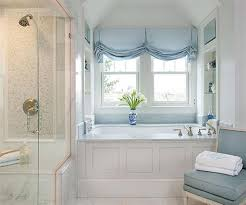 pretty bathroom with blue shades for the windows over drop in tub