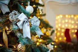 silver bow surrounded by other decorations on tree stock photo
