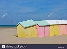 row of colourful beach cabins in pastel colours along the north