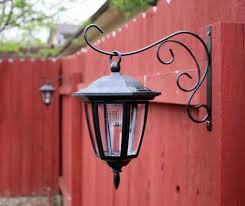 solar lights hung on plant hangers for your fence great idea