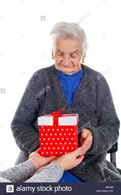 what to get an elderly woman for christmas picture of an elderly woman receiving a christmas gift stock photo
