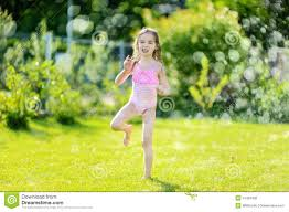 running though a sprinkler in a backyard stock photo image