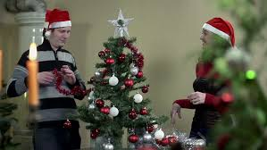 Decorate Christmas Tree Ribbon Video by Slow Motion Decoration Christmas Tree By Man And Woman Stock